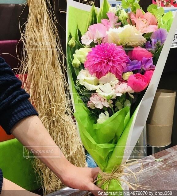 プレゼント用花束をアレンジしてくれたお花屋さんの手の写真・画像素材[4872870]