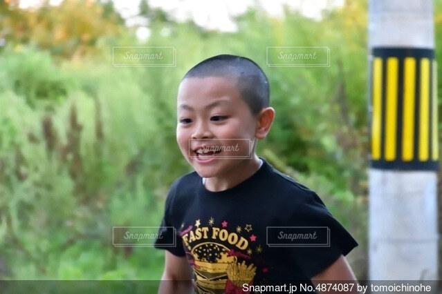 草の中に立っている小さな男の子の写真・画像素材[4874087]