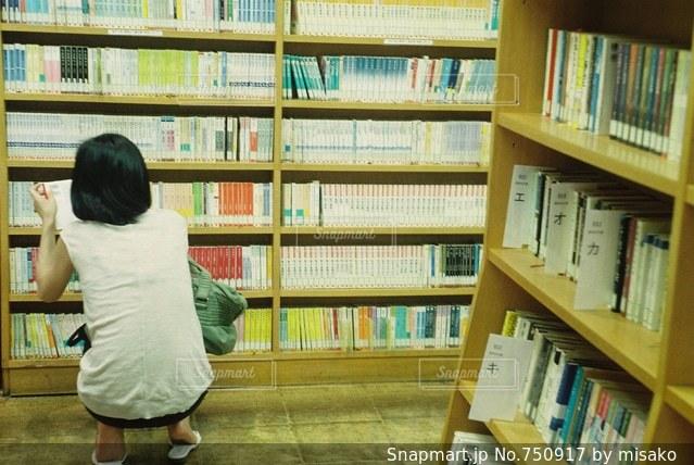 本の棚の前で座っている女の子の写真・画像素材[750917]
