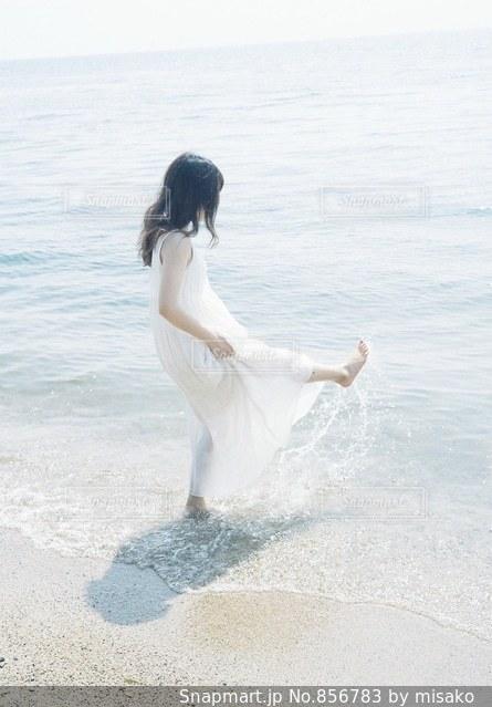水の体の横に立っている人の写真・画像素材[856783]
