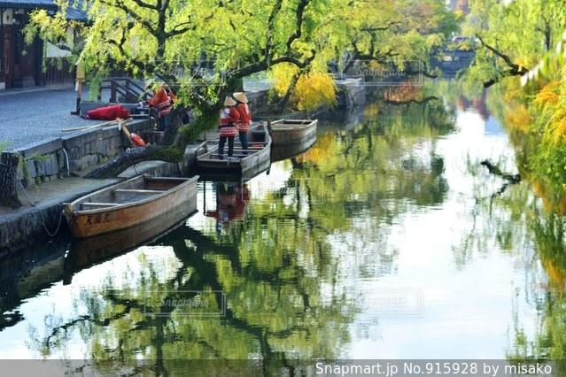 水の体の横に川に沿って浮遊船 - No.915928