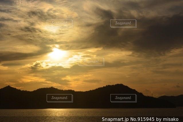 背景の山が付いている水の体に沈む夕日 - No.915945