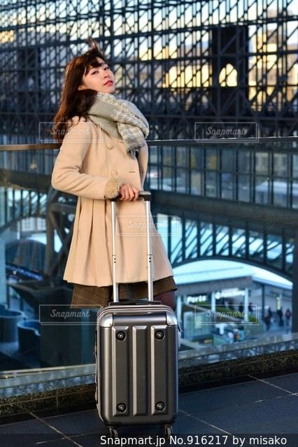 荷物の袋の横に立っている女性の写真・画像素材[916217]