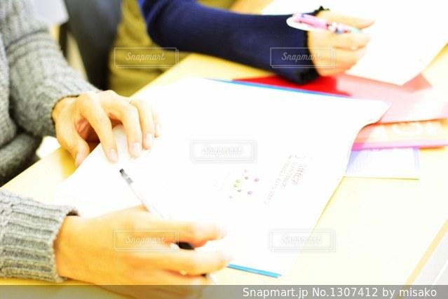 ラップトップを使用してテーブルに座っている人の写真・画像素材[1307412]