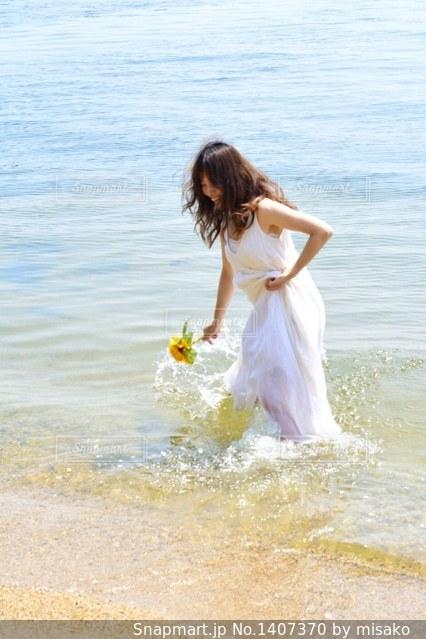 水の体の横に立っている人の写真・画像素材[1407370]