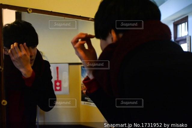 カメラにポーズ鏡の前に立っている男の写真・画像素材[1731952]