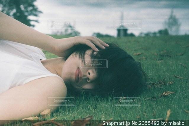 草の上に横たわる女性の写真・画像素材[2355492]