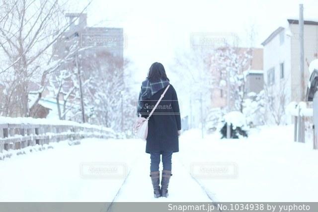 雪に覆われた通りの上を歩く人の写真・画像素材[1034938]