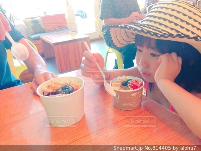 小さな女の子のテーブルに座っての写真・画像素材[814405]