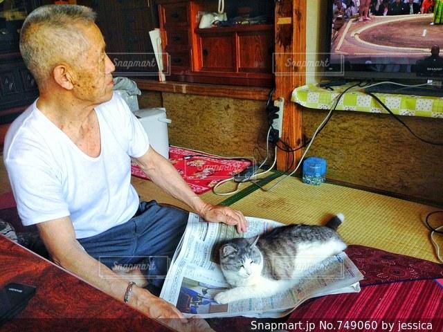 猫とテーブルに座っている男の人の写真・画像素材[749060]