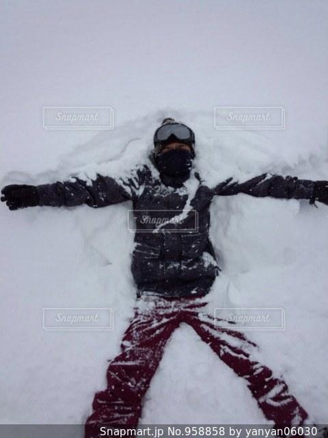 雪の中に大の字に寝るの写真・画像素材[958858]