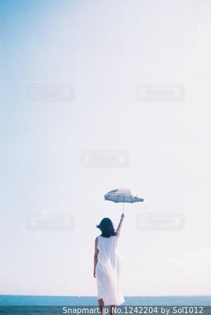 水の体の横に立っている人の写真・画像素材[1242204]