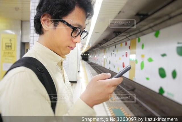 駅ホームでスマホを操作するカジュアルな男性の写真・画像素材[1263097]