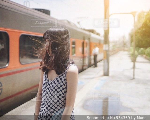 電車の横に立っている女性の写真・画像素材[934339]