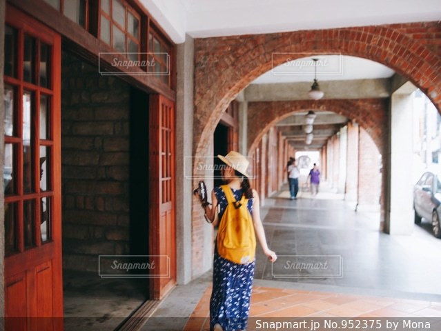 建物前の歩道を歩いている人の写真・画像素材[952375]