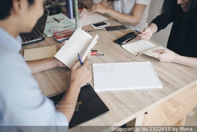 ラップトップを使用してテーブルに座っている人々 のグループの写真・画像素材[1322610]