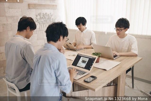 ラップトップ コンピューターを使用してテーブルに座っている人々 のグループの写真・画像素材[1323668]
