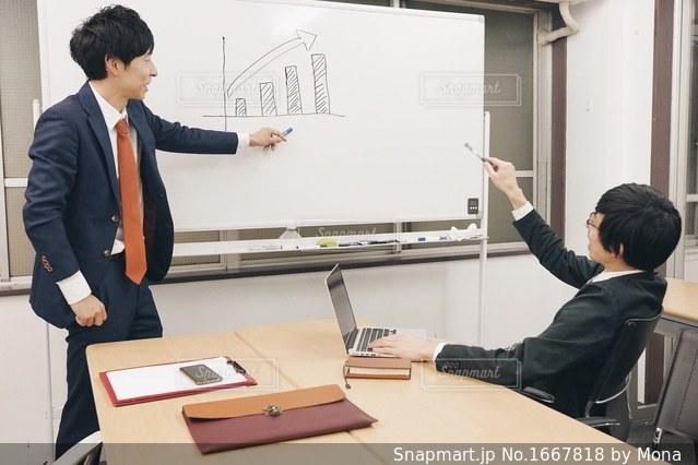 ホワイトボードに書いて説明するビジネスマンの写真・画像素材[1667818]