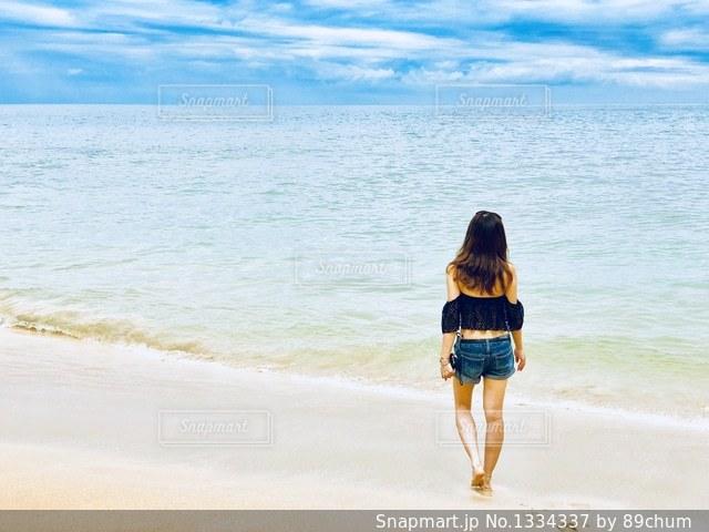 水の体の近くのビーチに立っている人の写真・画像素材[1334337]