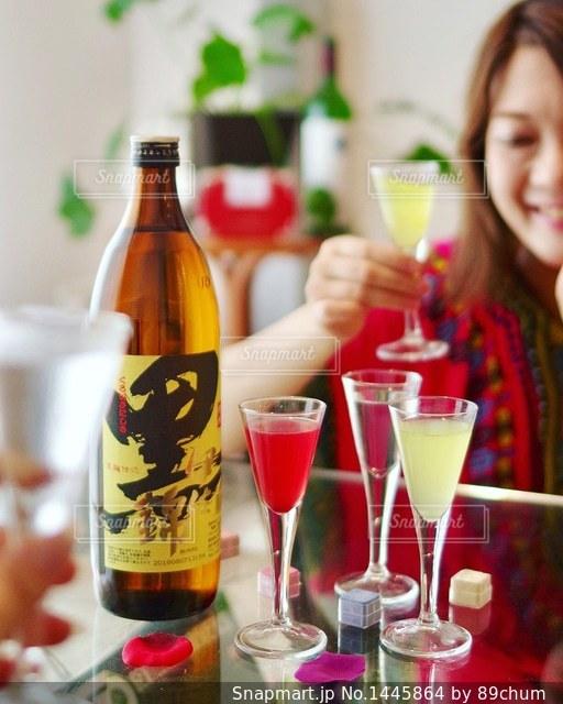 ワインのボトルでテーブルに座っている女性の写真・画像素材[1445864]