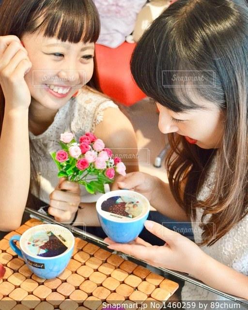 小さな女の子のテーブルに座っての写真・画像素材[1460259]