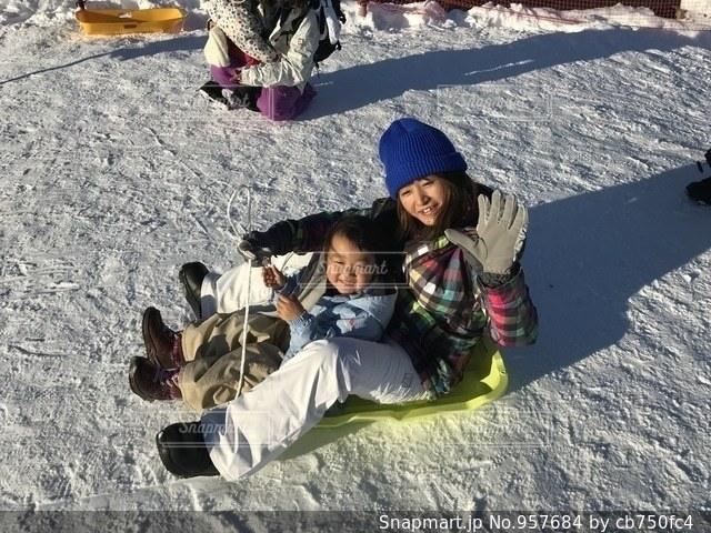雪の中で座っている小さな男の子 - No.957684