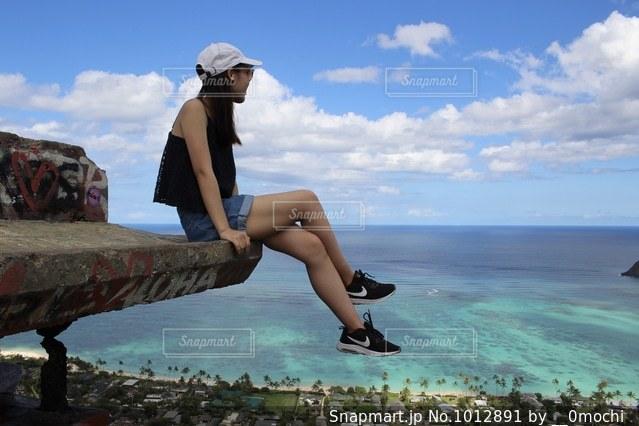 水の体の横に座っている人の写真・画像素材[1012891]