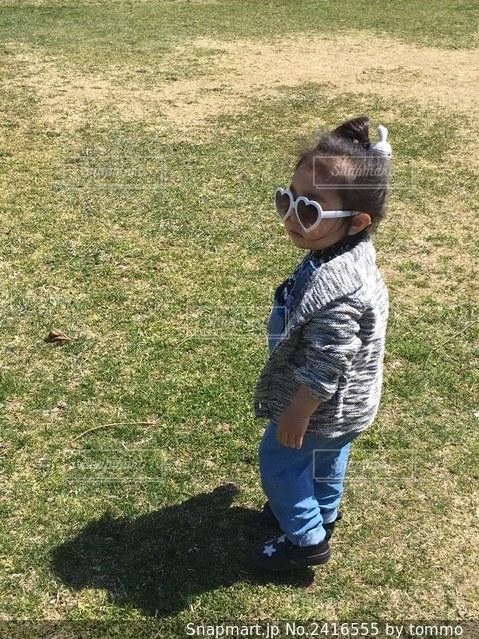 草の上に立っている小さな女の子の写真・画像素材[2416555]