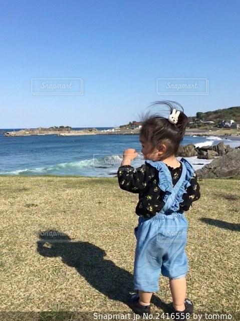 草の上に立っている小さな女の子の写真・画像素材[2416558]