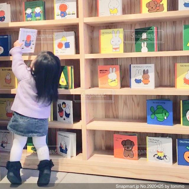 本棚の隣に立っている小さな女の子の写真・画像素材[2920425]