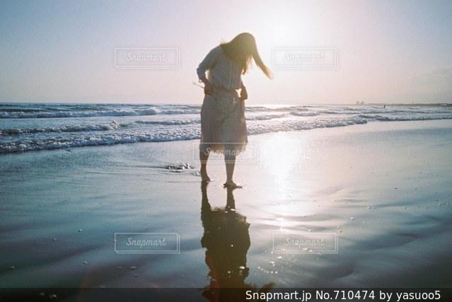 水の体の近くのビーチに立っている人 - No.710474