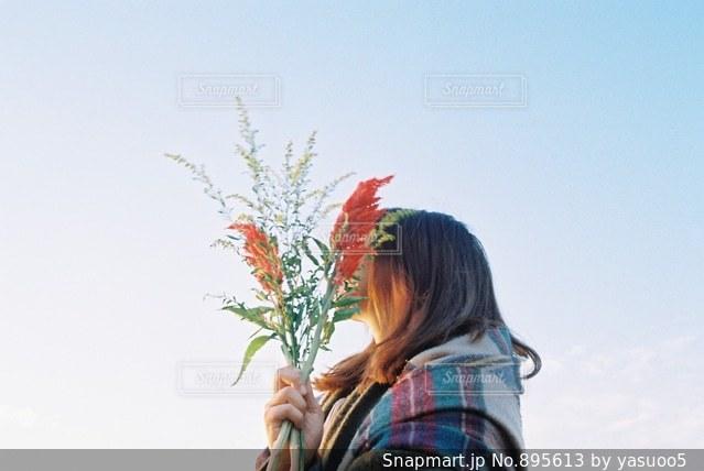 木の隣に立っている女性の写真・画像素材[895613]