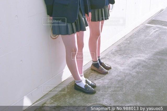 スーツケースの横に立っている女性の写真・画像素材[988013]