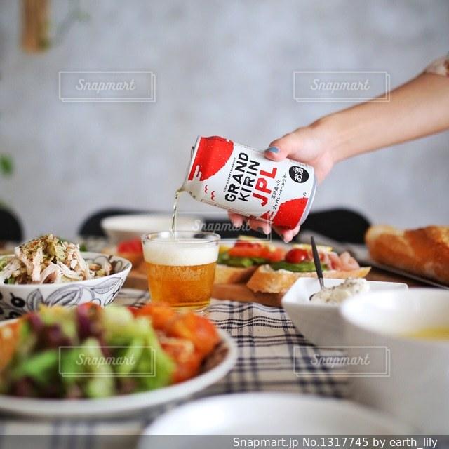 テーブルに食べ物のプレートを保持している女性の写真・画像素材[1317745]