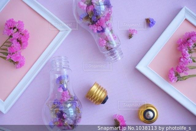 テーブルの上のピンクの花で一杯の花瓶の写真・画像素材[1038113]