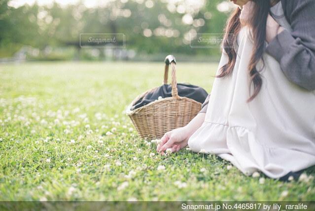 野原に座って花を摘む女性の写真・画像素材[4465817]