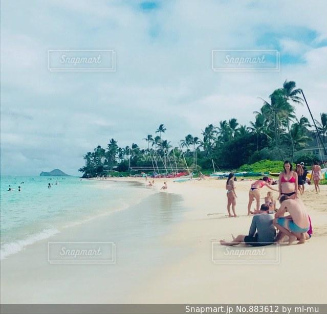 水の体の近くのビーチの人々 のグループ - No.883612