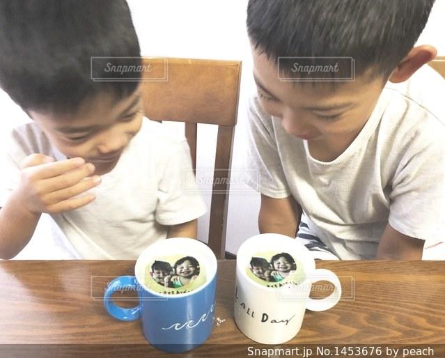 一杯のコーヒーをテーブルに座って若い男の子の写真・画像素材[1453676]