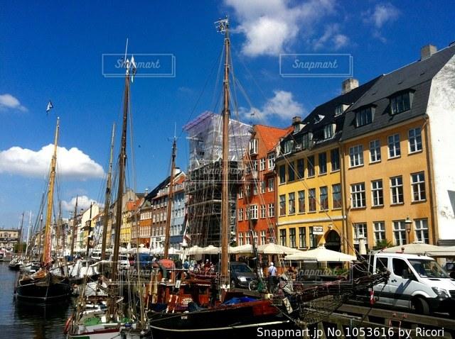 バック グラウンドで市と水の体中の小型船の写真・画像素材[1053616]
