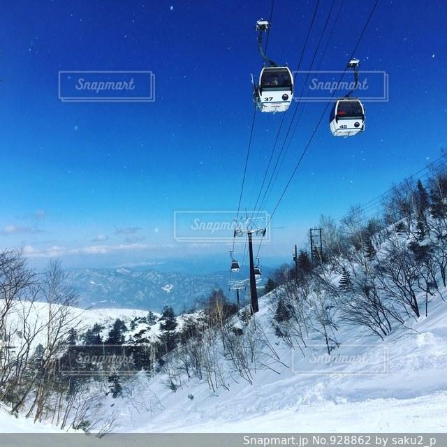 雪の上に空気を通って飛んで男覆われた斜面 - No.928862