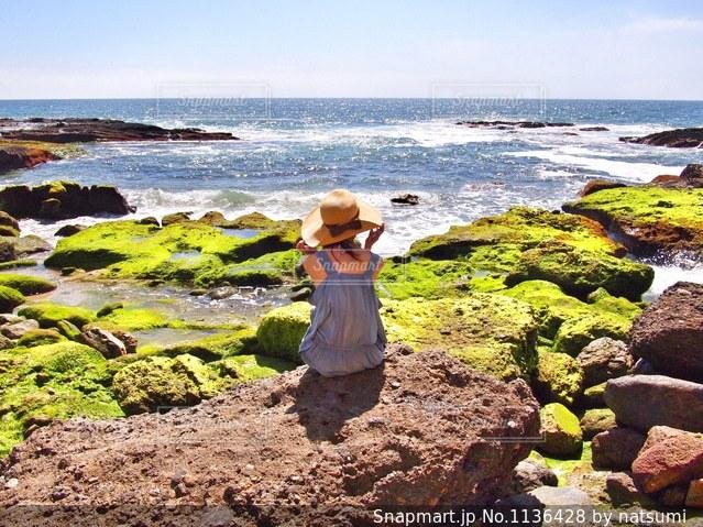 ビーチに座っている女性の後ろ姿の写真・画像素材[1136428]