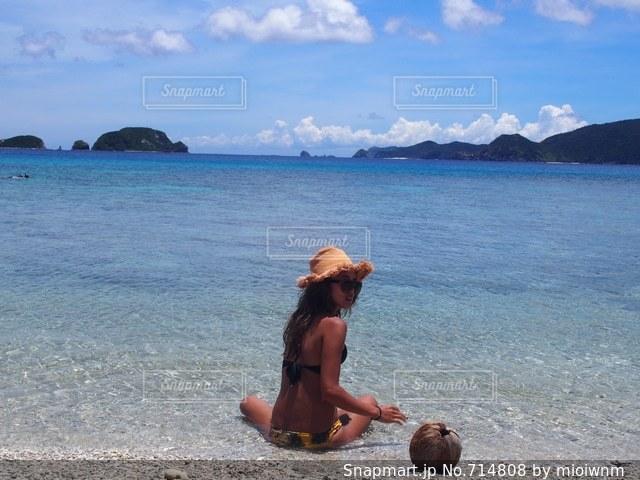 水の体の近くのビーチに座っている男 - No.714808