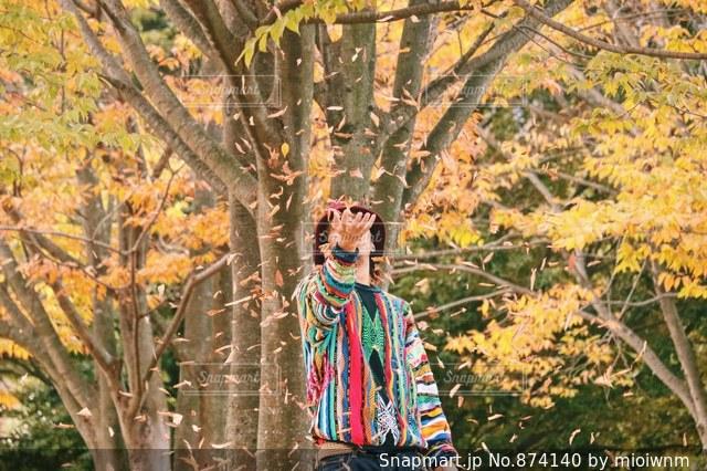木の隣に立っている人の写真・画像素材[874140]
