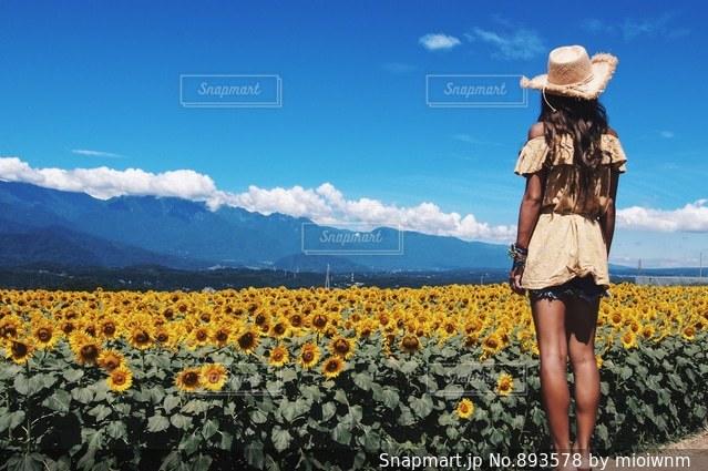 黄色の花の前に立っている女性 - No.893578