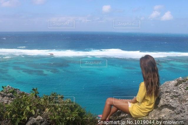 水の体の横に立っている人の写真・画像素材[1019044]