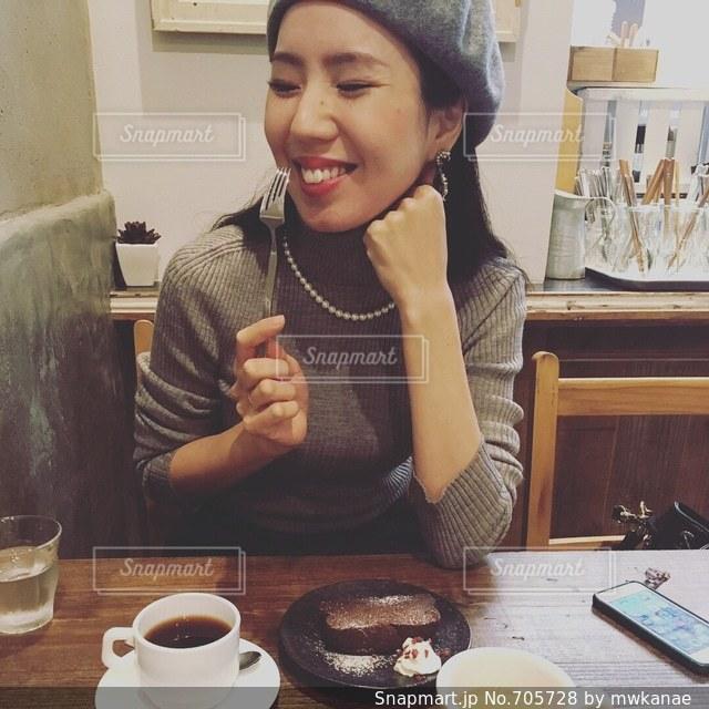 一杯のコーヒーをテーブルに座っている女性の写真・画像素材[705728]