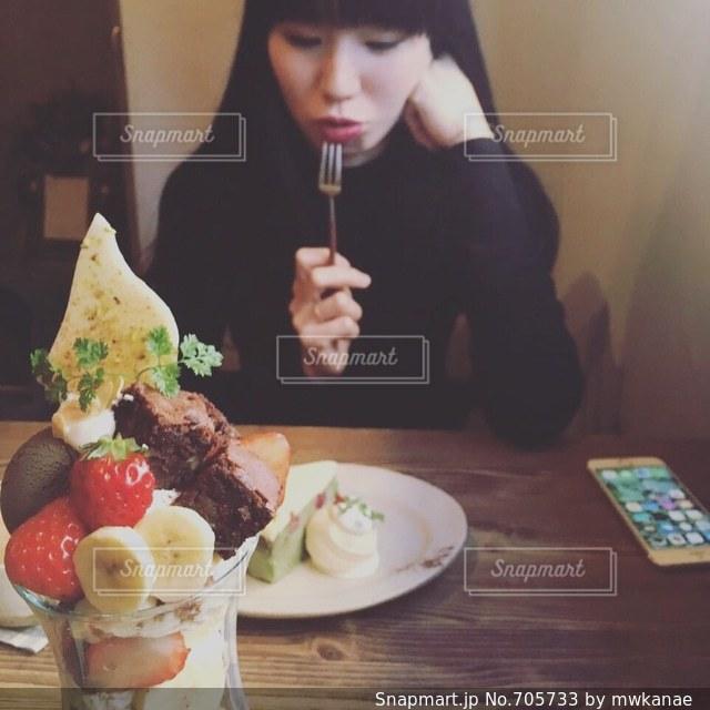 食品のプレートをテーブルに座っている女性の写真・画像素材[705733]