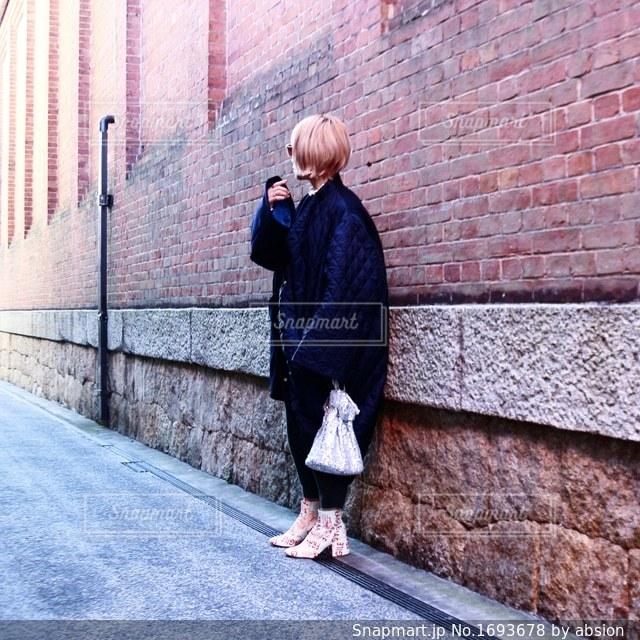 れんが造りの建物の前に立っている男の写真・画像素材[1693678]
