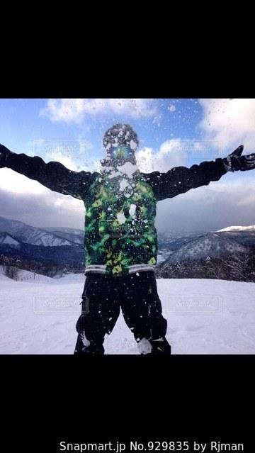 雪に覆われた斜面に立っている人 - No.929835