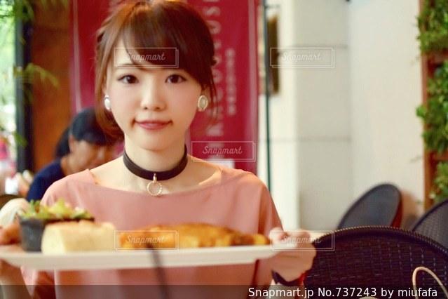 食品のプレートをテーブルに座っている少女 - No.737243